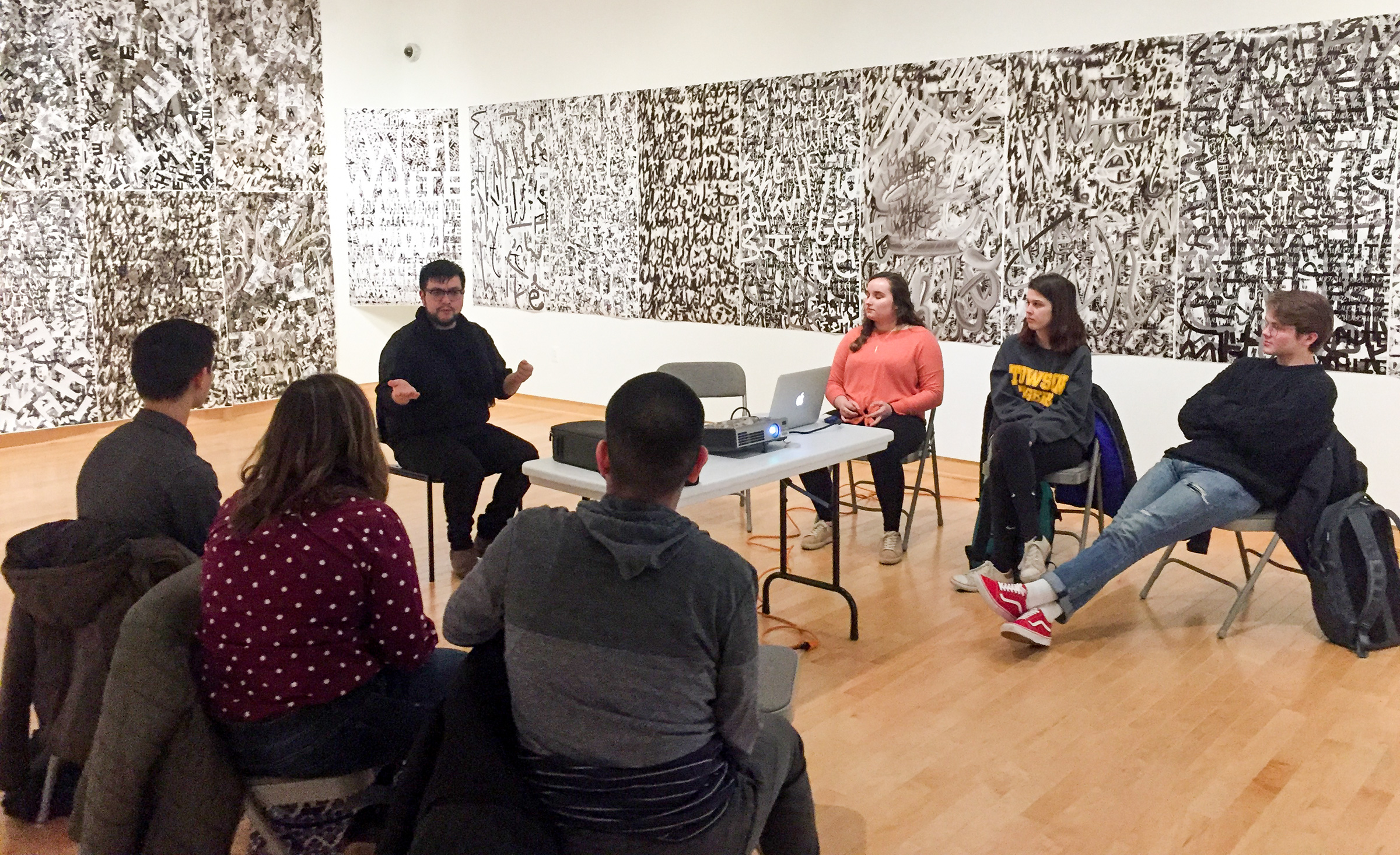 A small group of students meets with a recent Visiting Artist